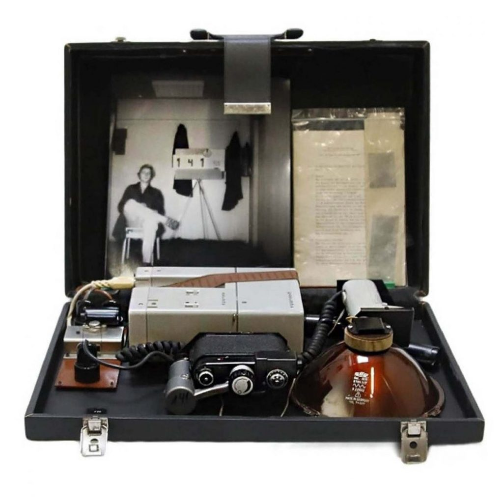 Valise du STASI (services secrets de la RDA) équipée d'une caméra spéciale et d'un illuminateur infrarouge invisible pour la photographie clandestine, vers 1970. Ce système permet de prendre des photos de nuit ou par temps de brouillard. La photographie, prise dans l'obscurité totale, montre un technicien du STASI en train de tester cet équipement (valise numérotée 141). © Marché Dauphine - Photo Sixtine Legrand